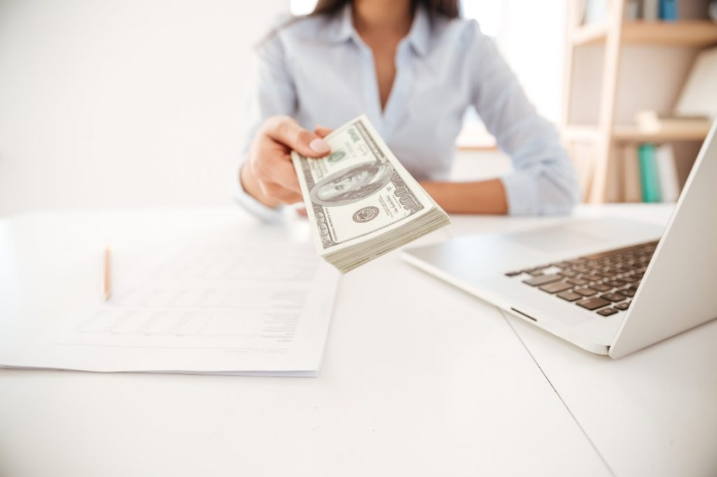 woman handing money to camera