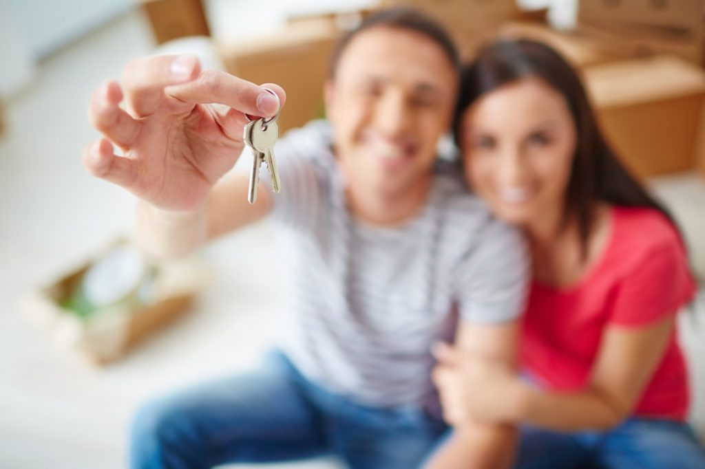 man and woman with keys to home